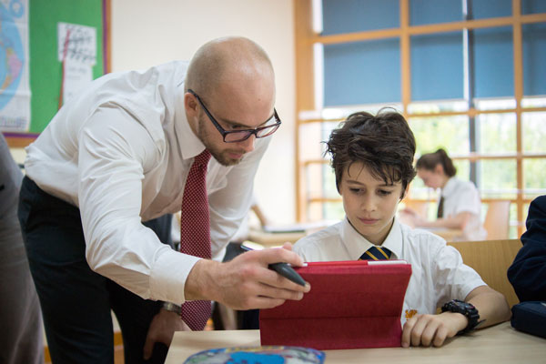 Teacher helping student with iPad